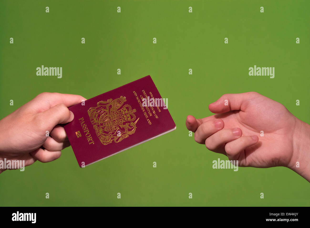 Hands exchanging a passport isolated on a green-screen background - Stock Image