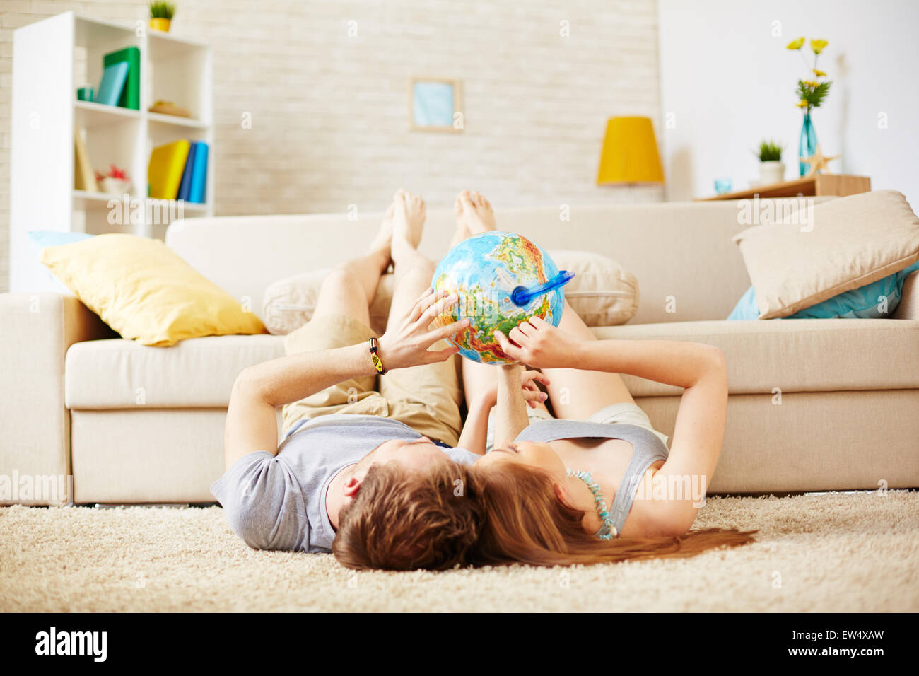 Relaxed couple choosing place on globe where to travel - Stock Image