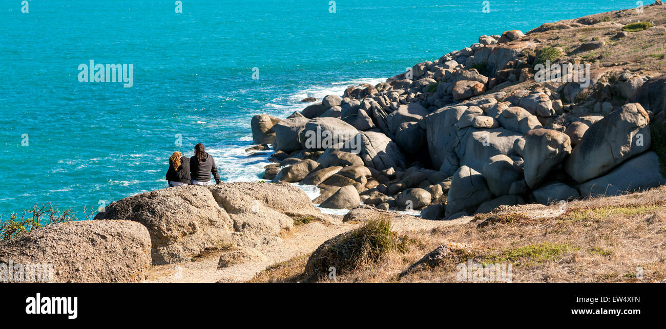 Two girls sitting on the rock of Granite Island, Victor Harbor. Warm tones - Stock Image