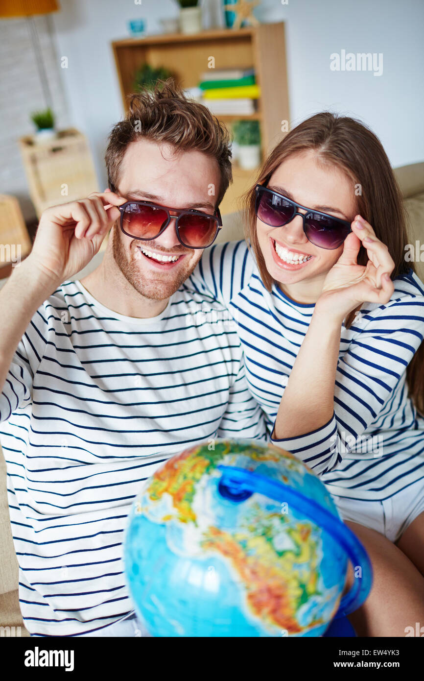 Amorous couple in sunglasses looking at camera with toothy smiles - Stock Image