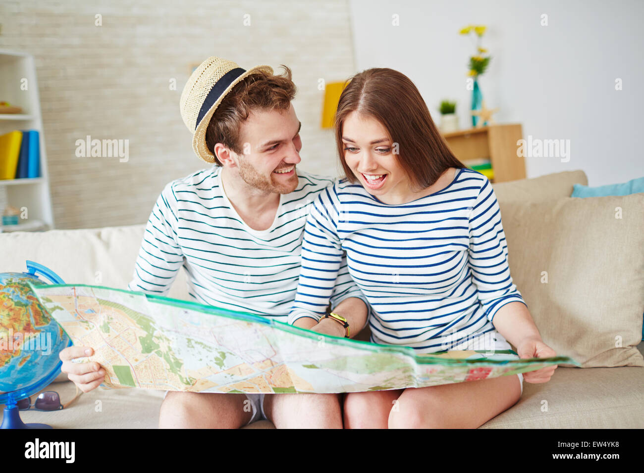 Young couple looking at map while choosing place for summer rest - Stock Image
