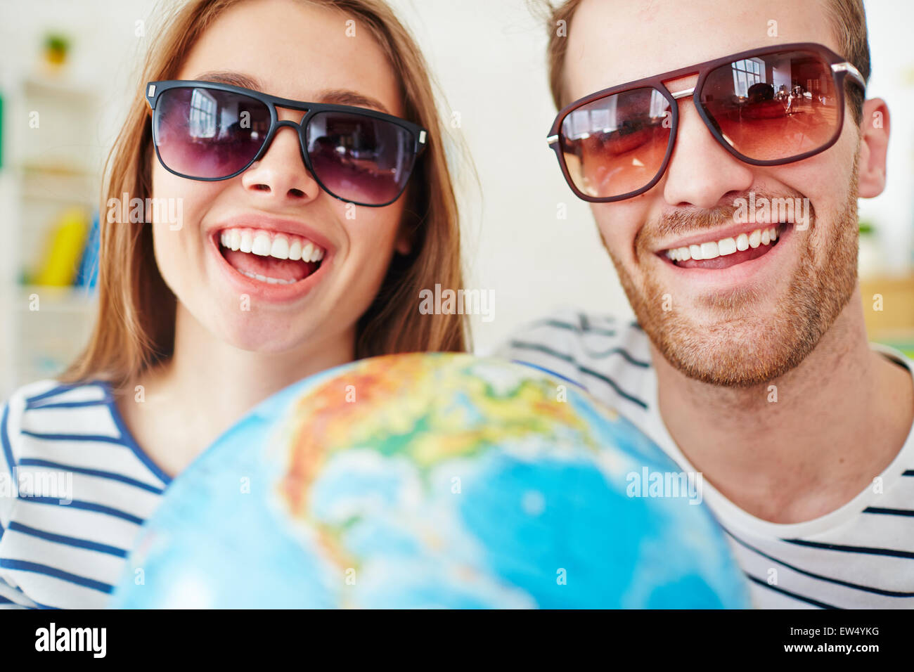 Happy dates looking at camera through sunglasses with toothy smiles - Stock Image
