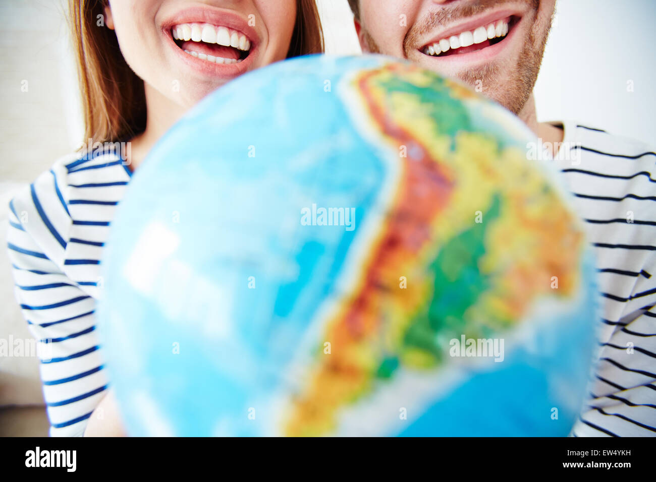 Close-up of toothy smiles of couple and globe - Stock Image