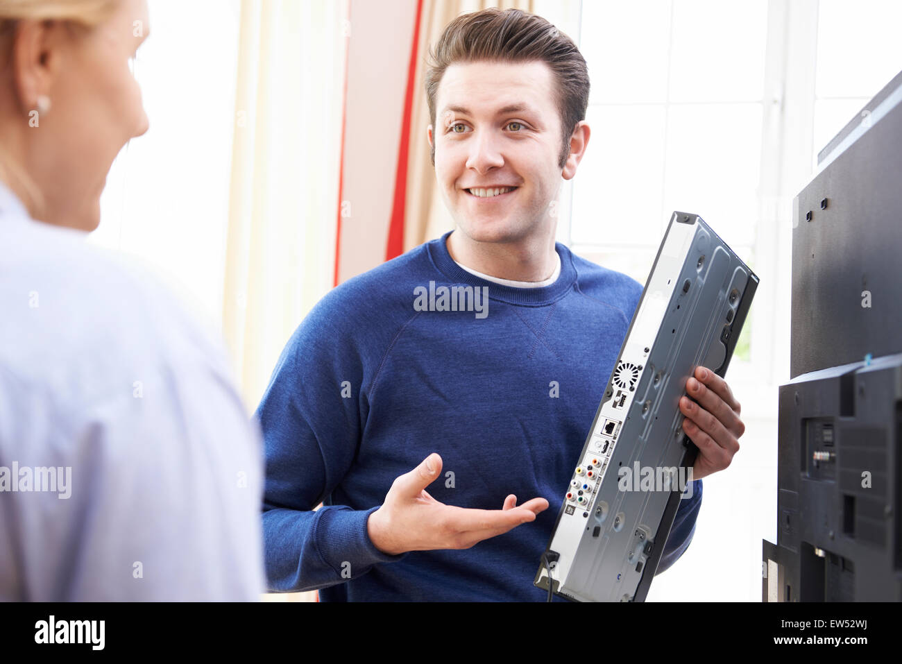 Engineer Giving Advice On Installing Digital TV Equipment - Stock Image