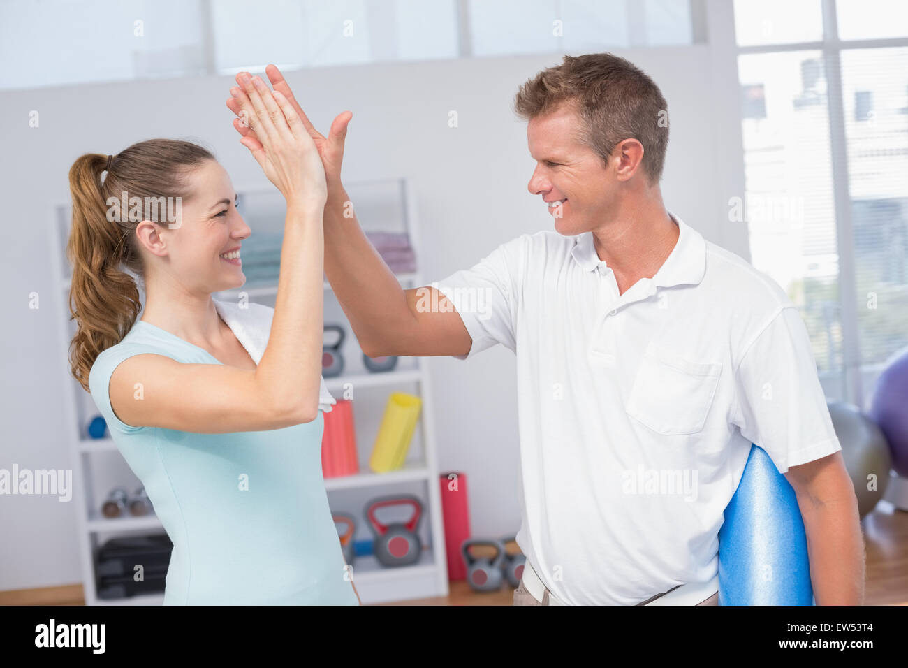 Woman celebrating with her trainer - Stock Image