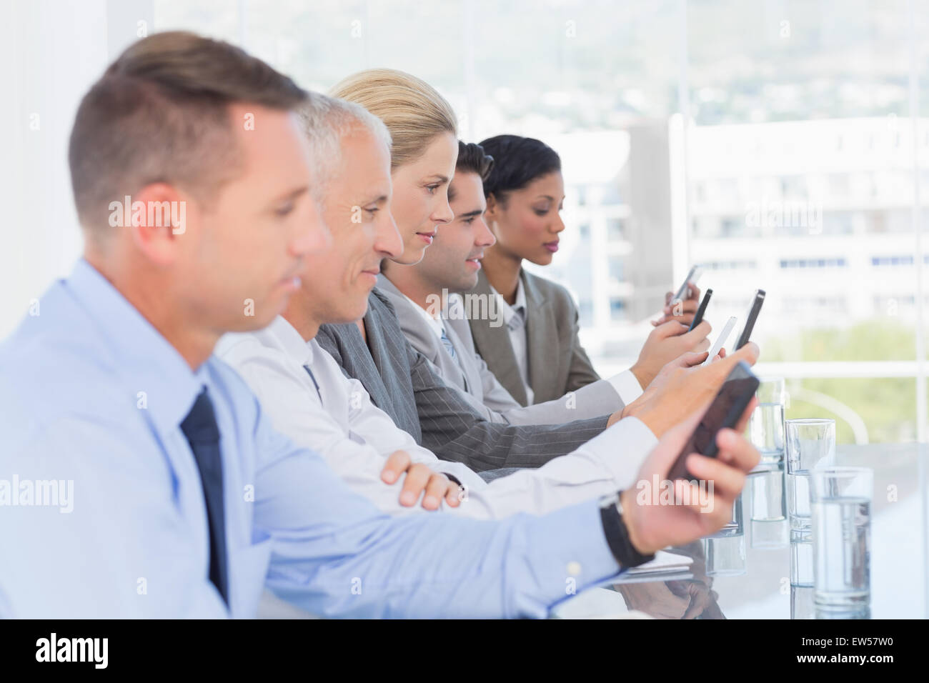 Business team using their mobile phone - Stock Image