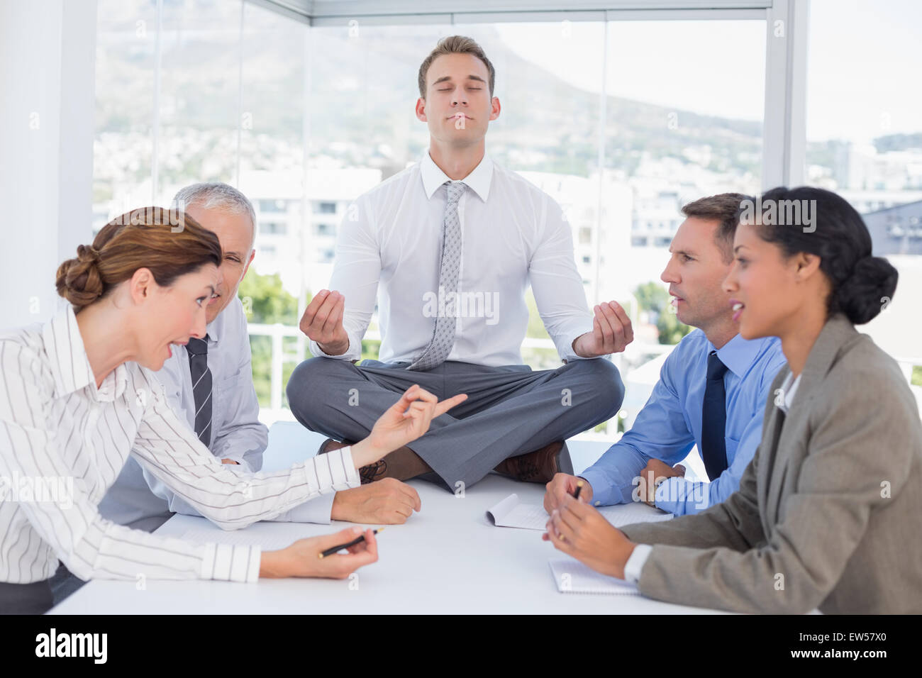 Businessman relaxing on the desk with upset colleagues around - Stock Image