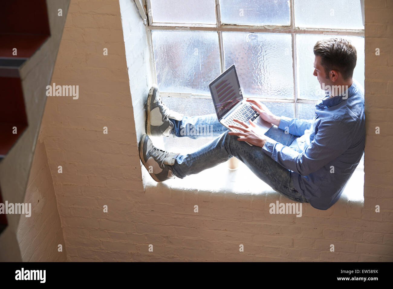 Casually Dressed Businessman Working On Stairs In Office - Stock Image