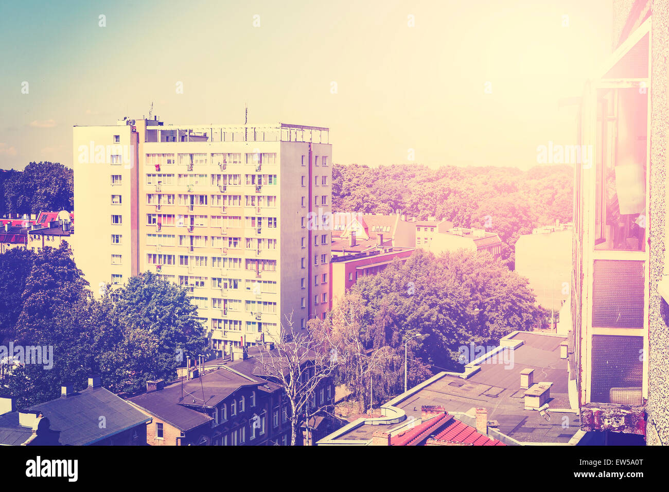 Retro toned picture of residential block apartments at sunset, nature and housing coexistence concept. Stock Photo