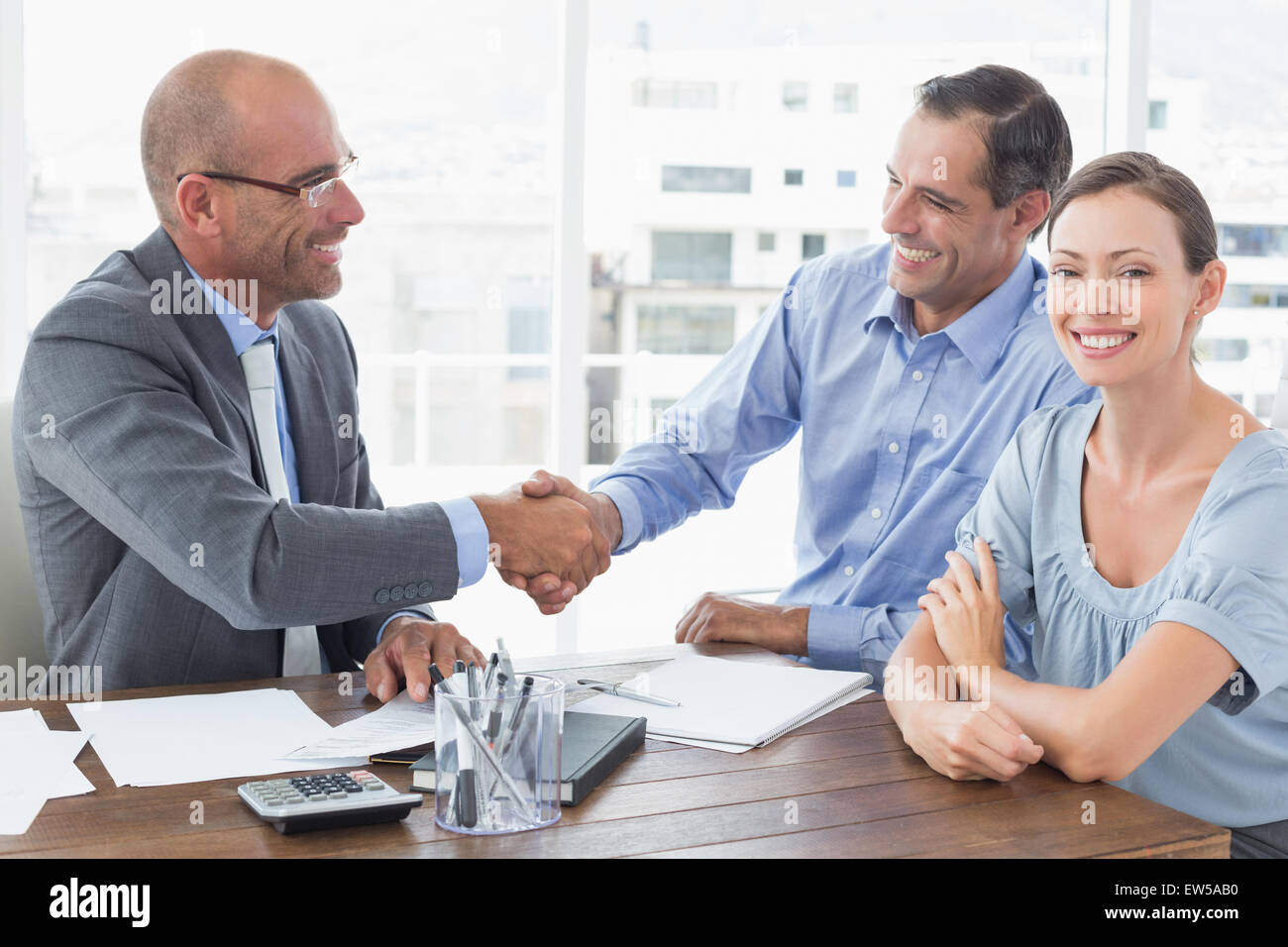 Businessman shaking hands with a co worker - Stock Image
