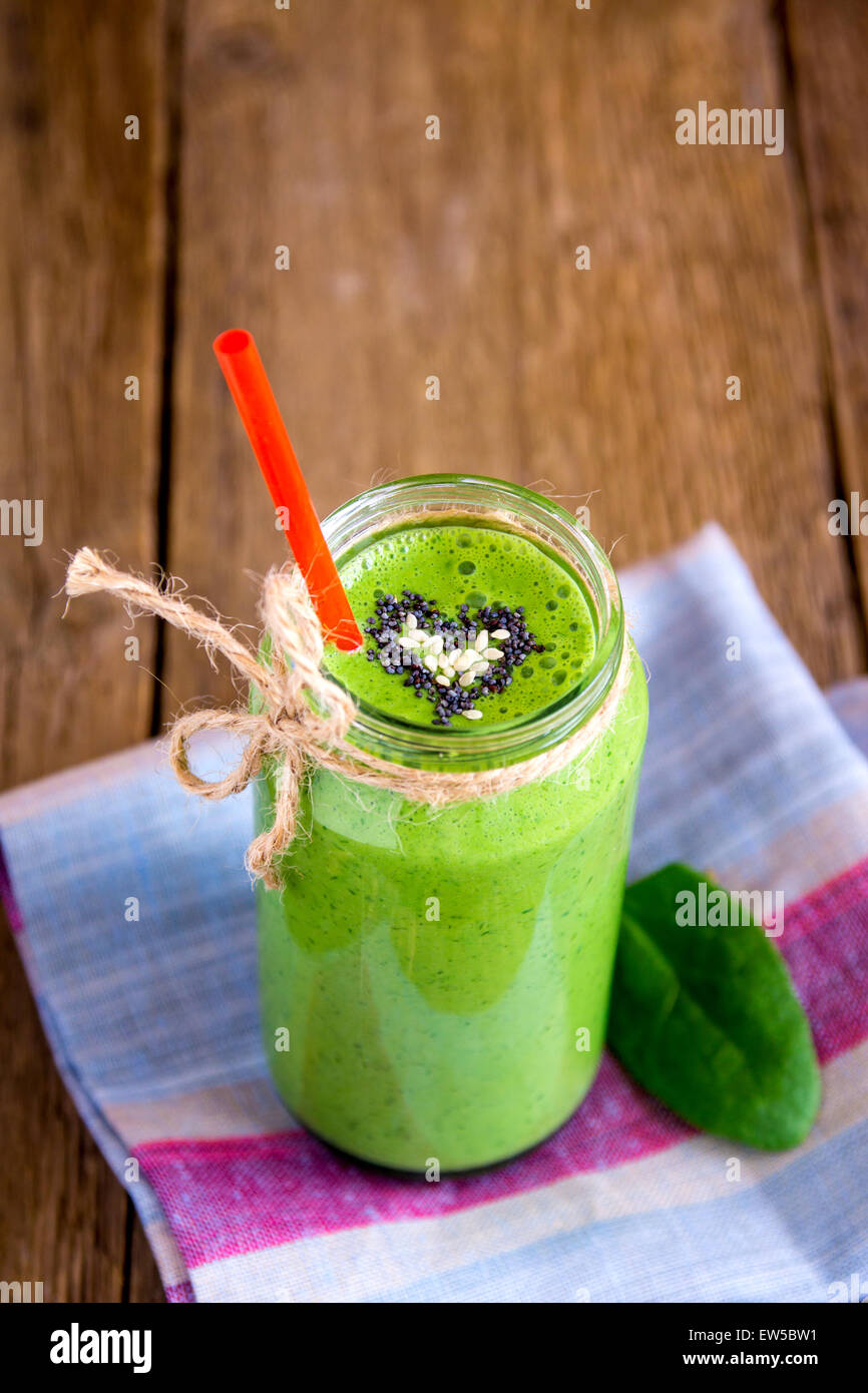 Green vegetable and herbs smoothie with heart of poppy and sesame seeds. Love for a healthy raw food concept. - Stock Image