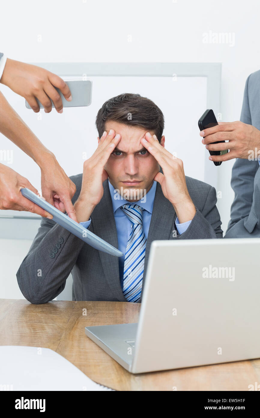 Worried businessman with head in hands - Stock Image