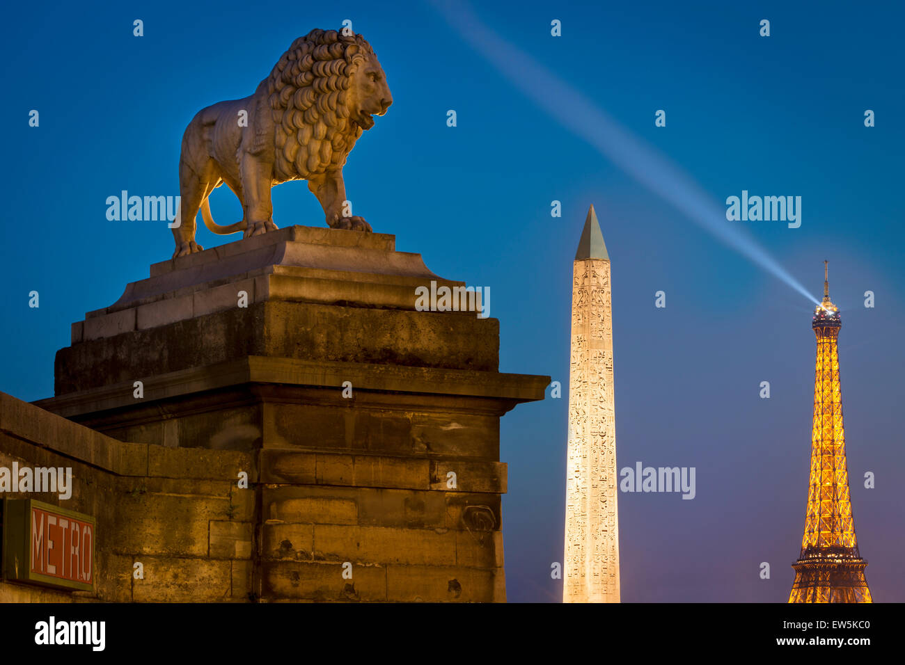 Lion statue overlooking the Egyptian Obelisk at Place de la Concorde and Eiffel Tower, Paris, France - Stock Image