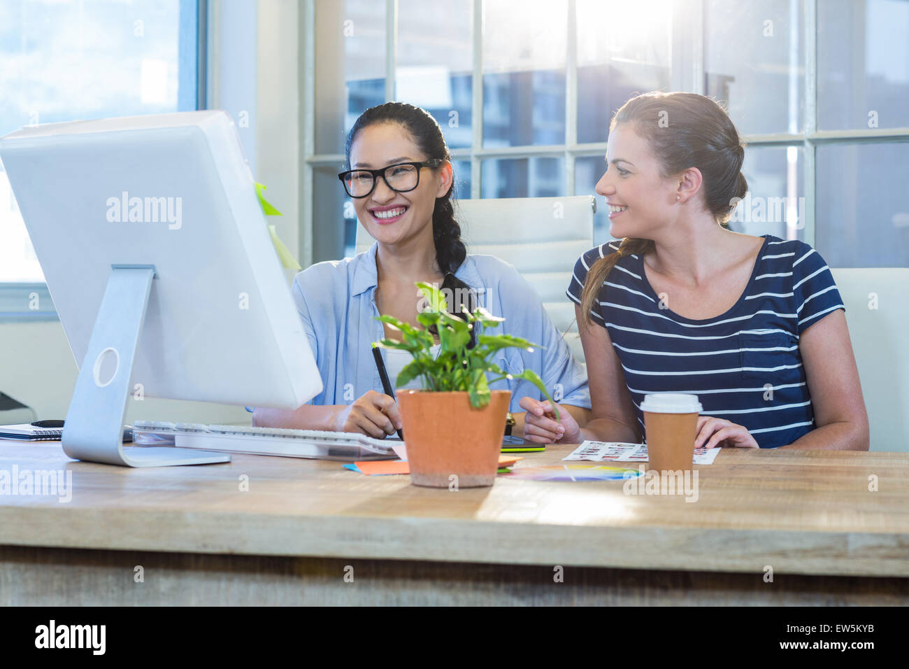 Smiling partners working together with photographs and digitizer - Stock Image