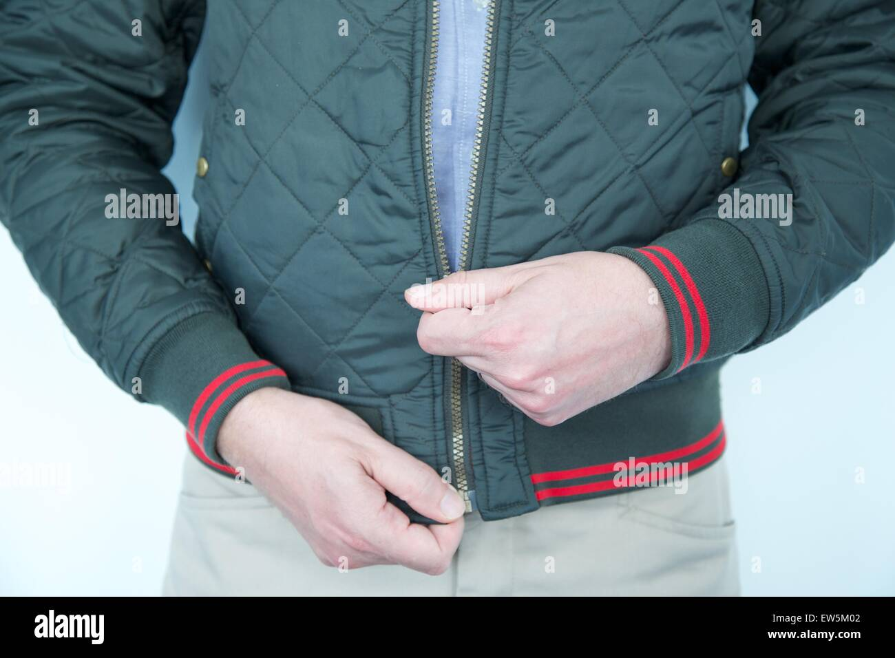 Young, white caucasian male zipping up his jacket - Stock Image
