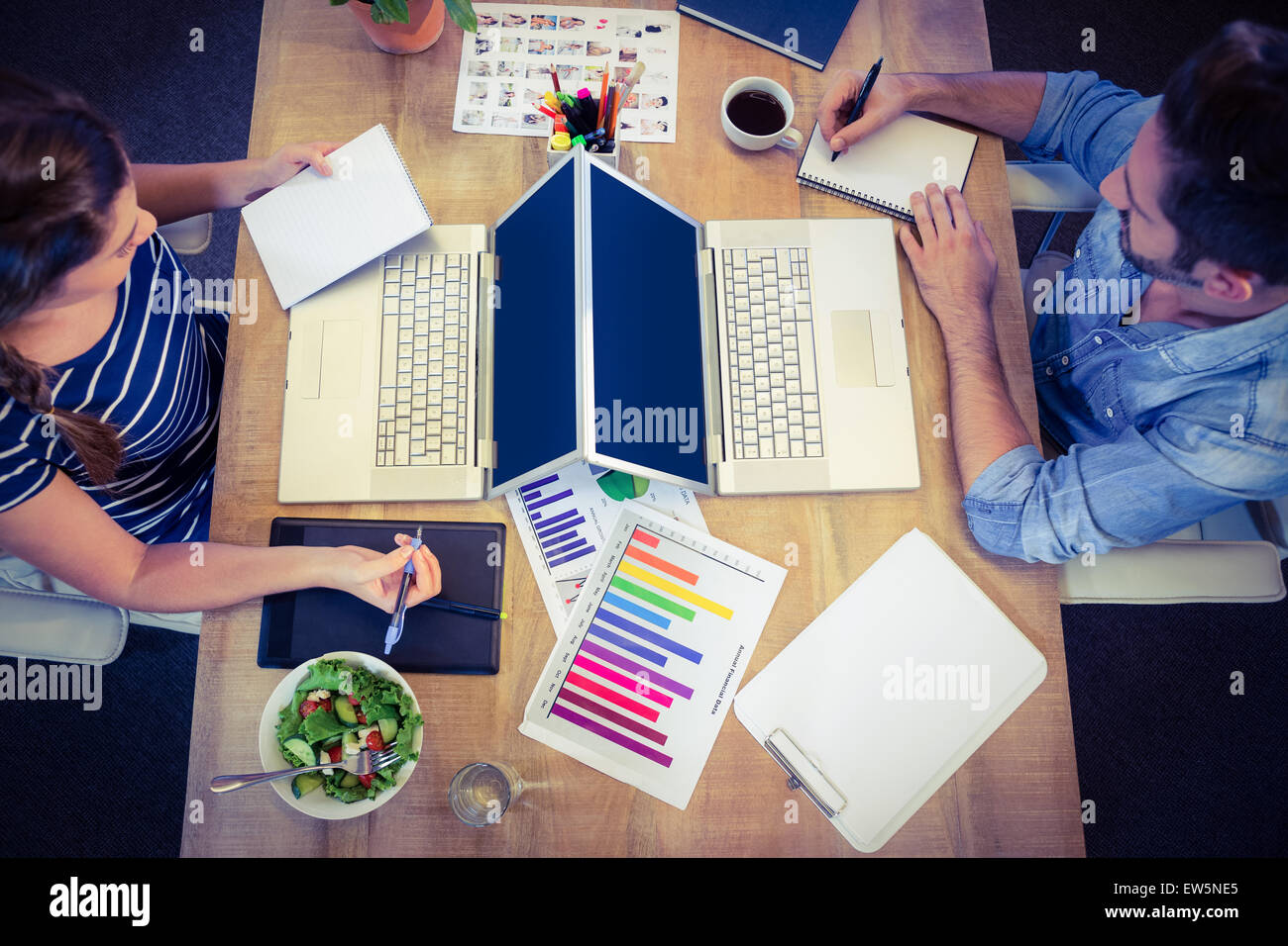 Happy creative workers sharing desk - Stock Image