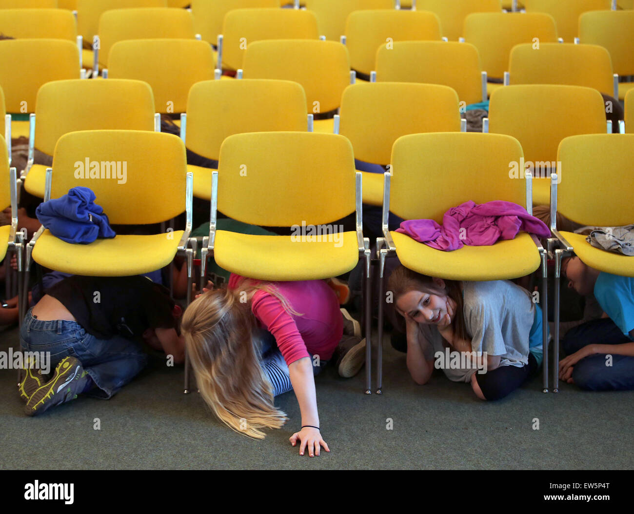 Aachen, Germany. 18th June, 2015. Students seek protection under auditorium seats during an earthquake drill in - Stock Image