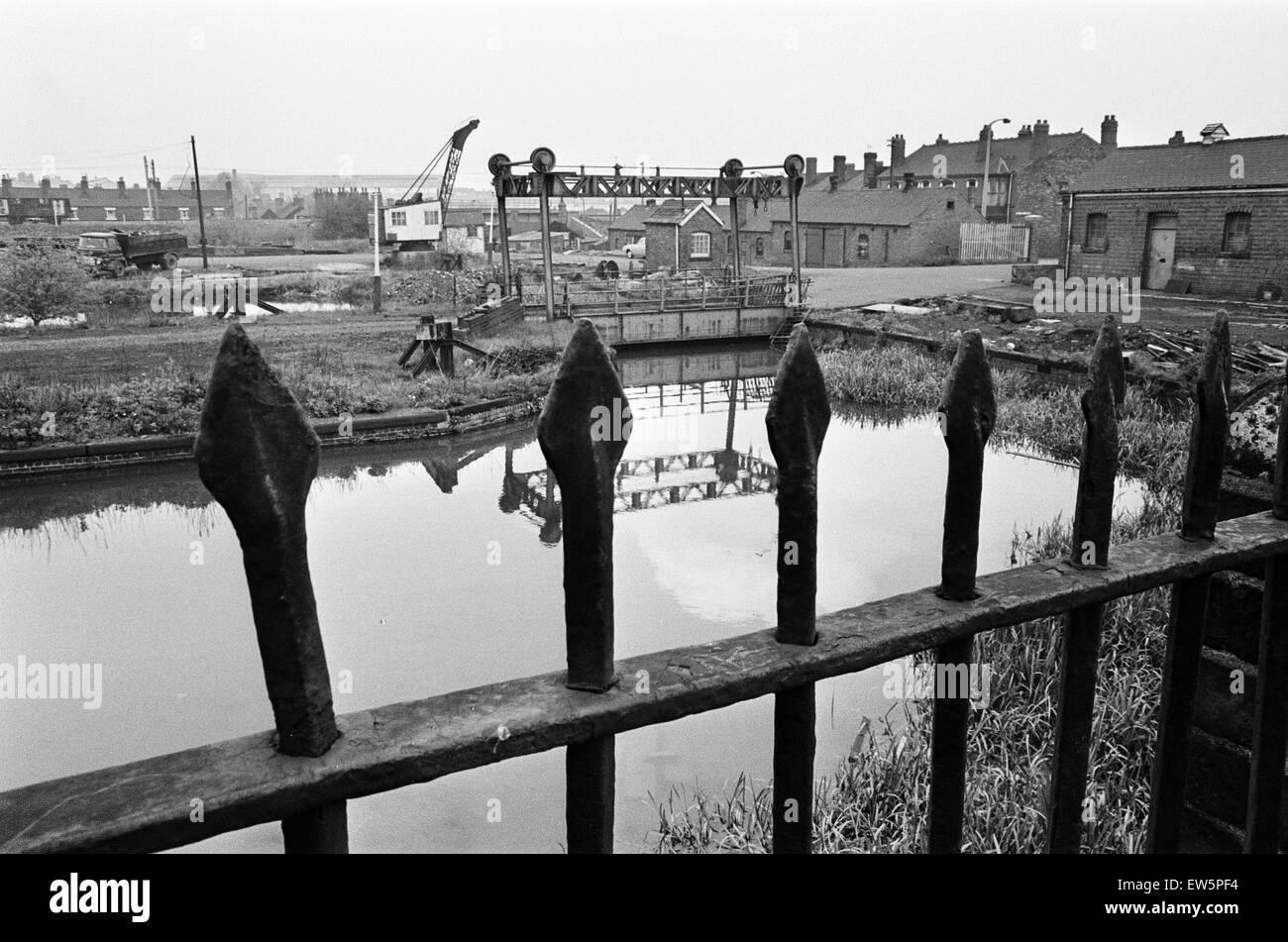 Railings, blackened by 150 years of industrial smoke separate the weed grown banks of the Birmingham Wolverhampton - Stock Image