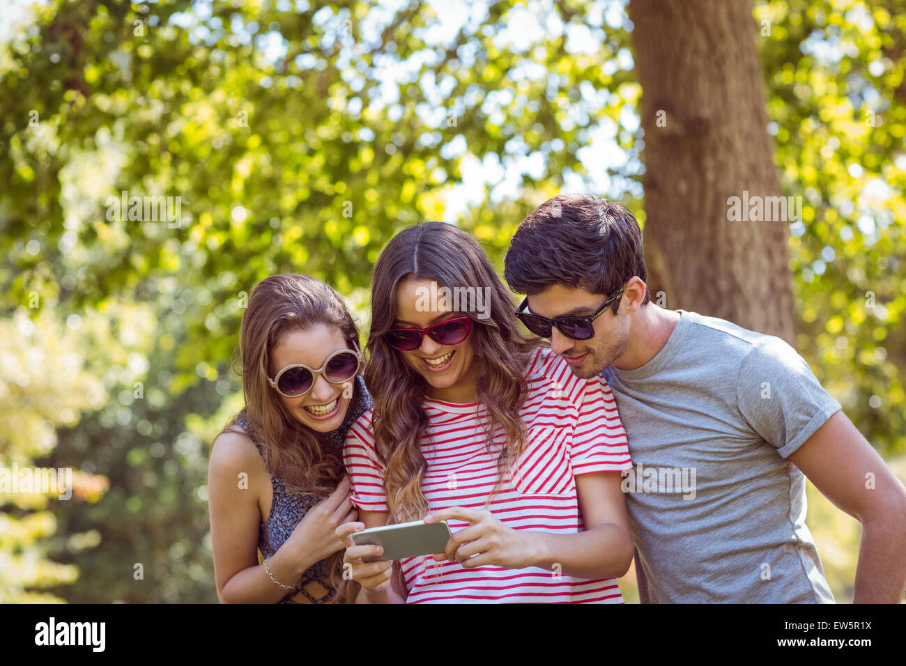 friends looking photos in a park - Stock Image