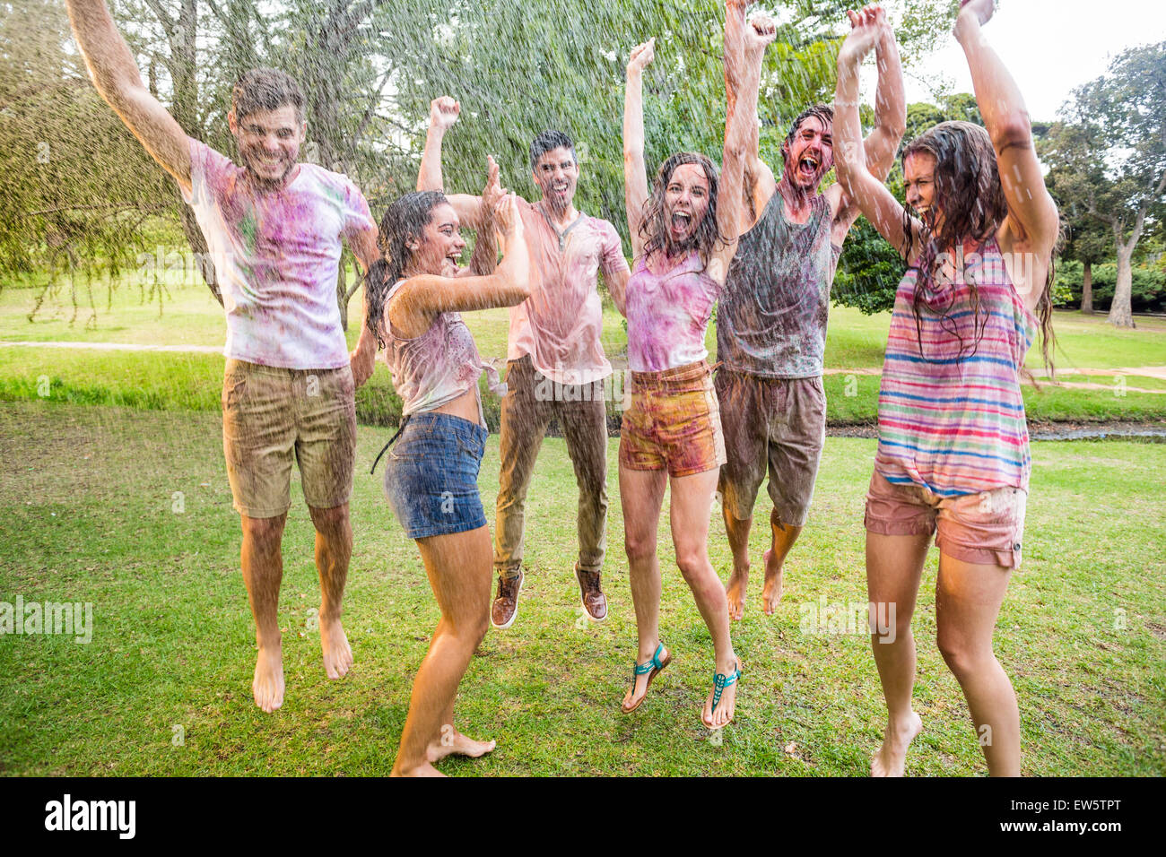 Happy friends jumping in the water shoot - Stock Image