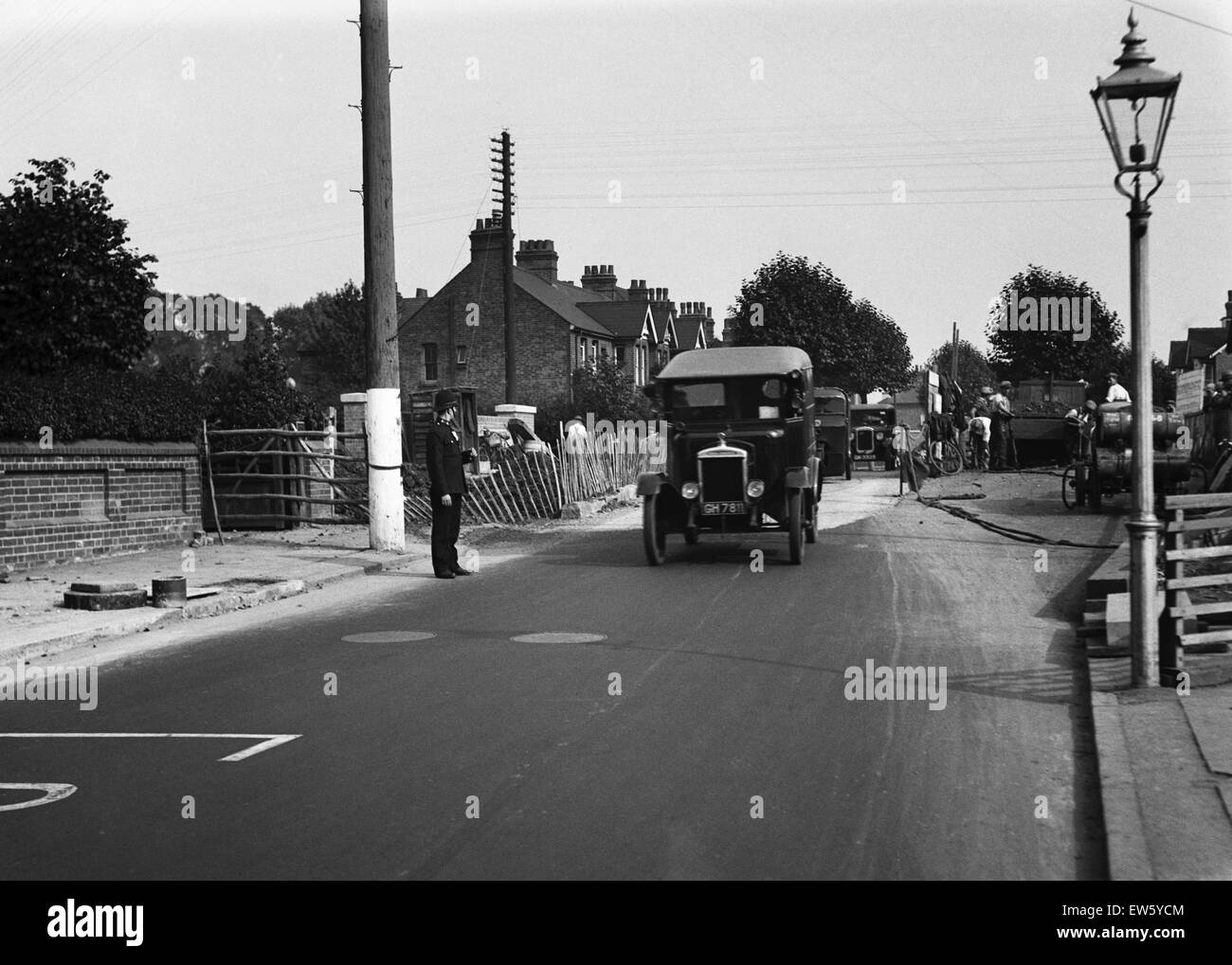 Police direct traffic as workmen repair the road in an unknown location in Uxbridge, London. Circa 1931 - Stock Image