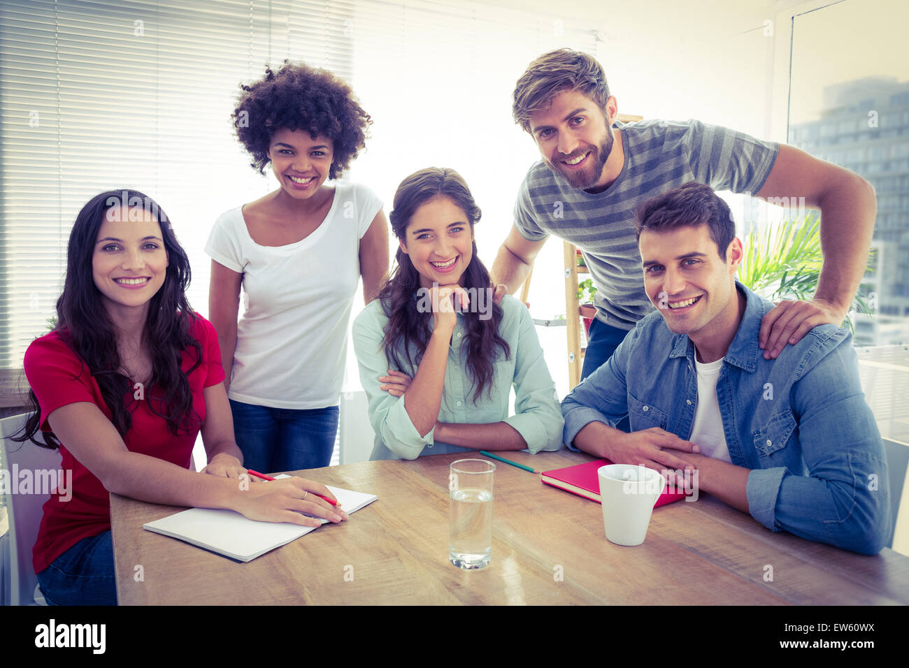 Portrait of a smiling business team looking at the camera - Stock Image