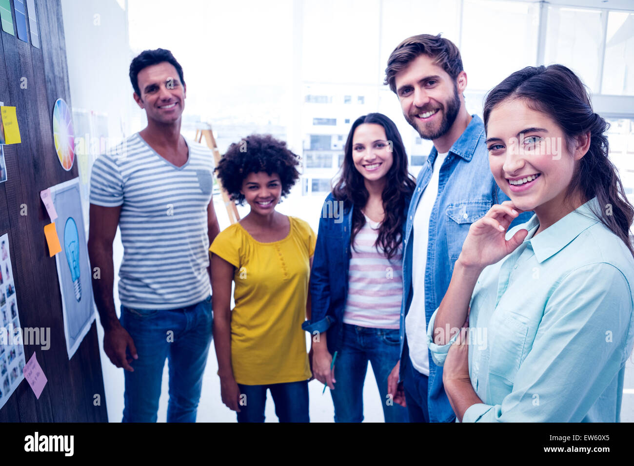 Young creative business people at work by blackboard - Stock Image
