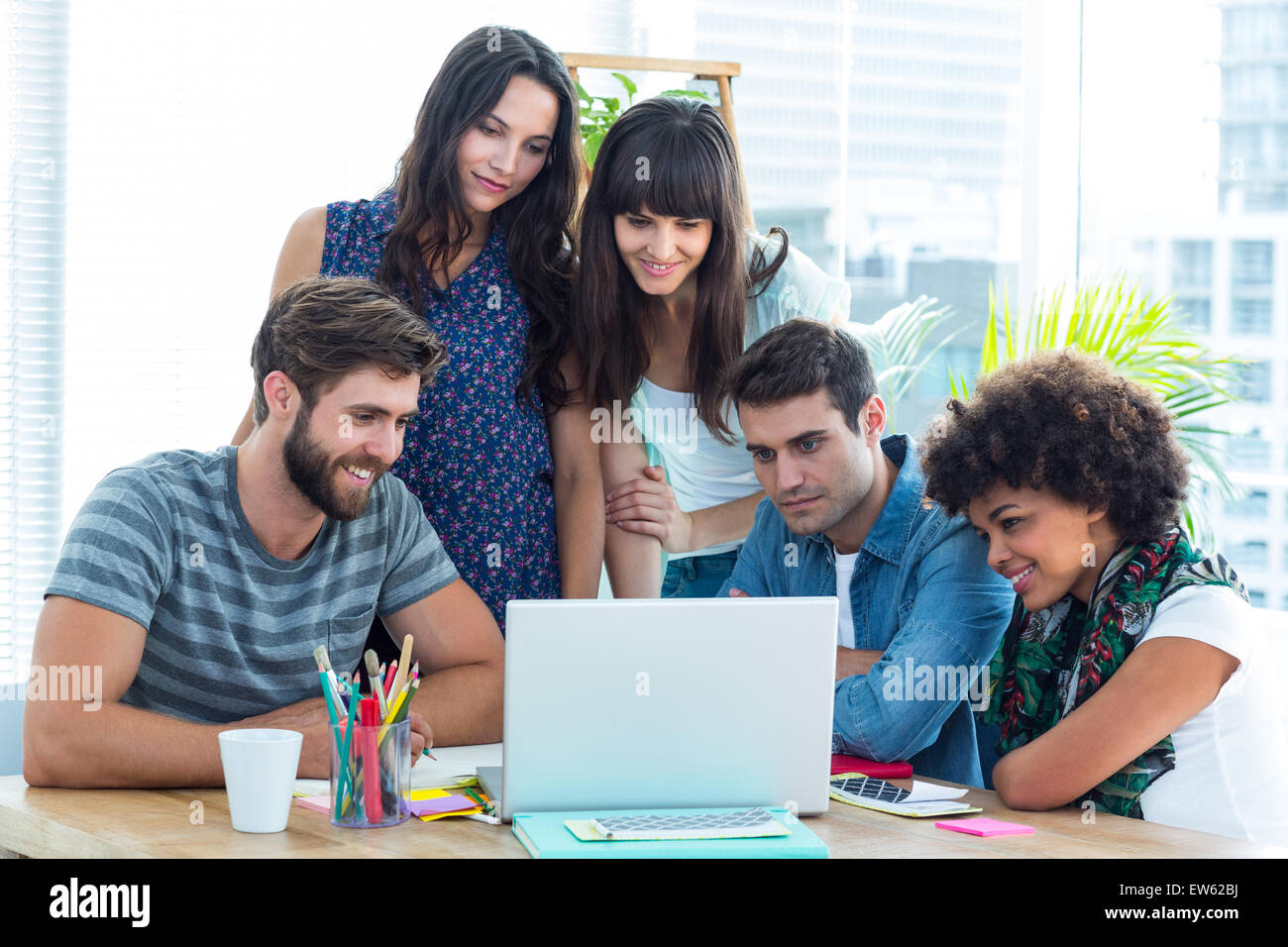 Happy creative business team gathered around a laptop - Stock Image