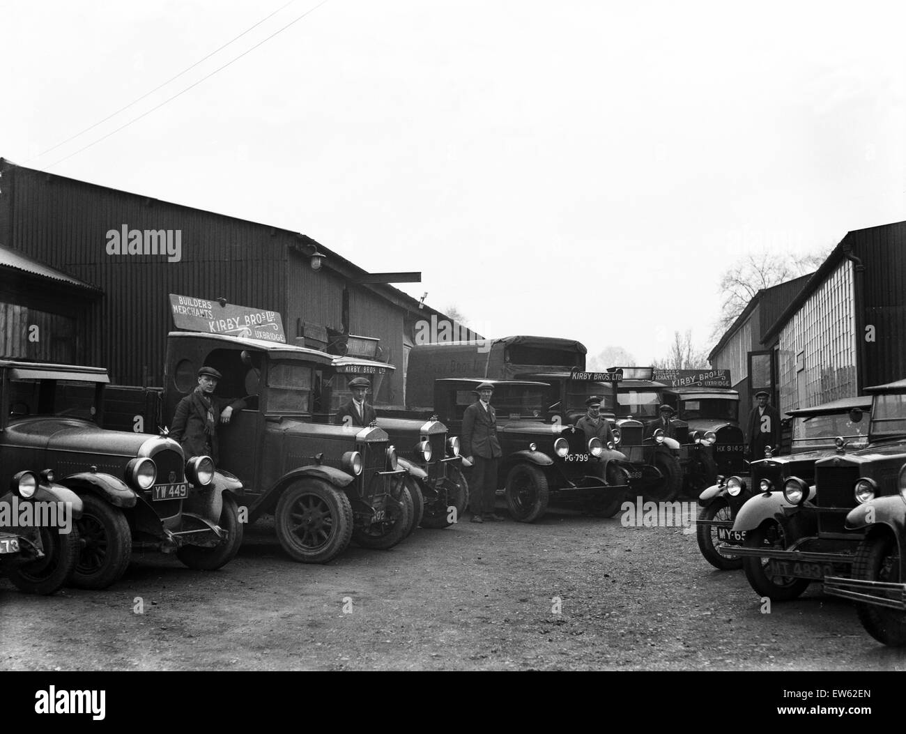 The staff of Uxbridge builders merchants Kirby Brothers pose beside their lorries and vans, London. Circa 1930 - Stock Image