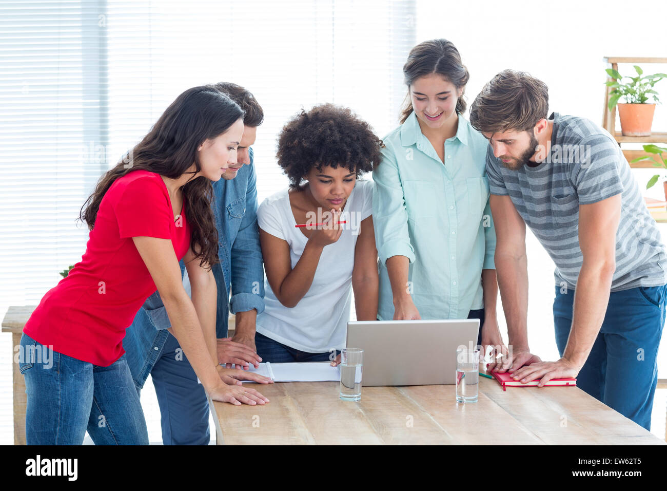 Colleagues gathered around a laptop at office - Stock Image