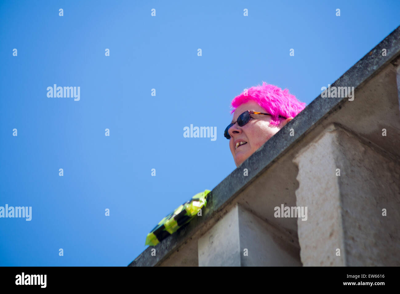 Woman with pink hair wearing sunglasses looking over wall at Weymouth, Dorset in June - Stock Image