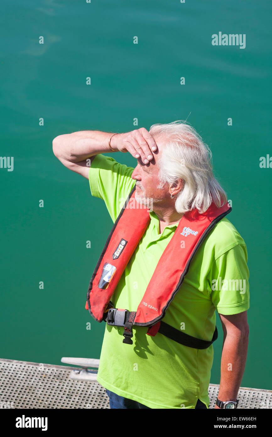 Man stood on pontoon wearing life vest at Weymouth, Dorset in June - Stock Image