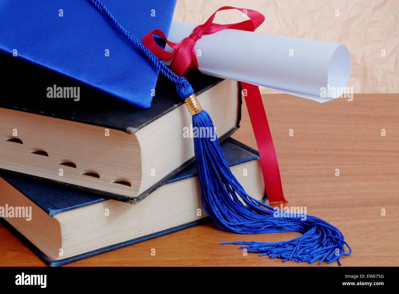 Graduation cap with books and diploma on a table - Stock Image