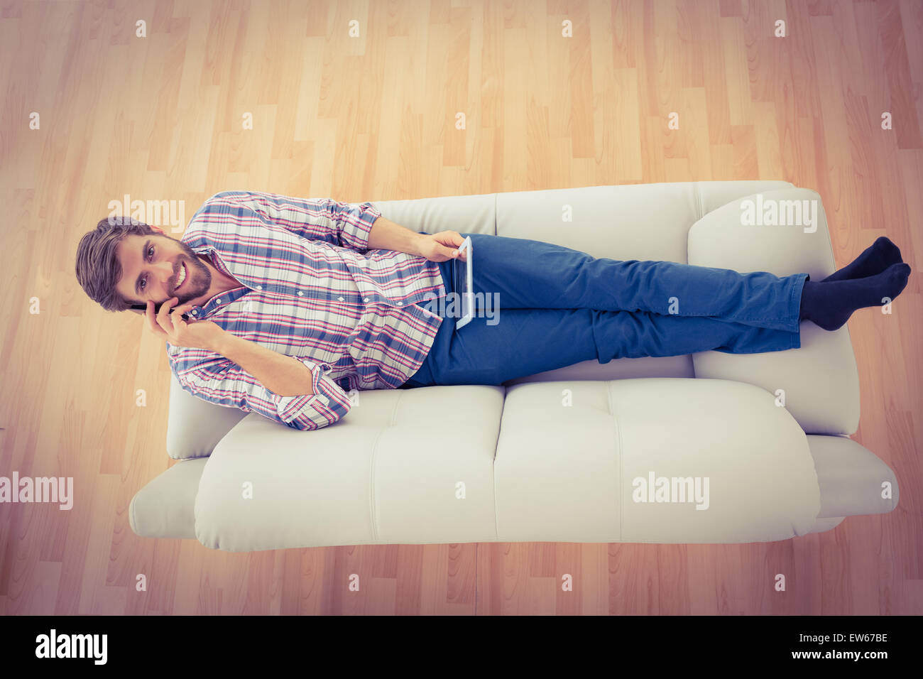 Businessman on the phone extended on the sofa - Stock Image
