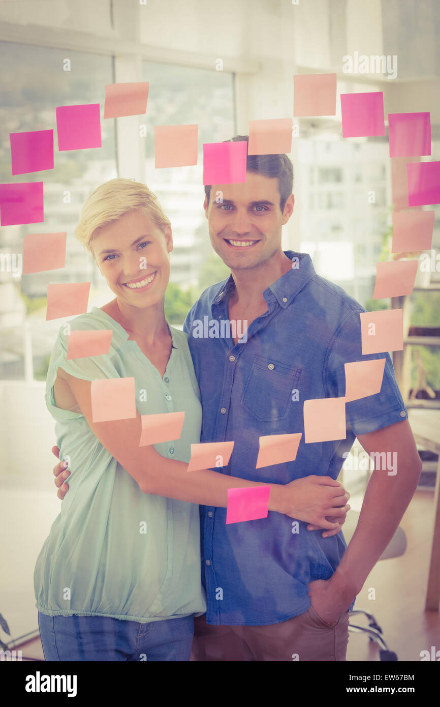 Business partners posing in front of pink heart posts it - Stock Image