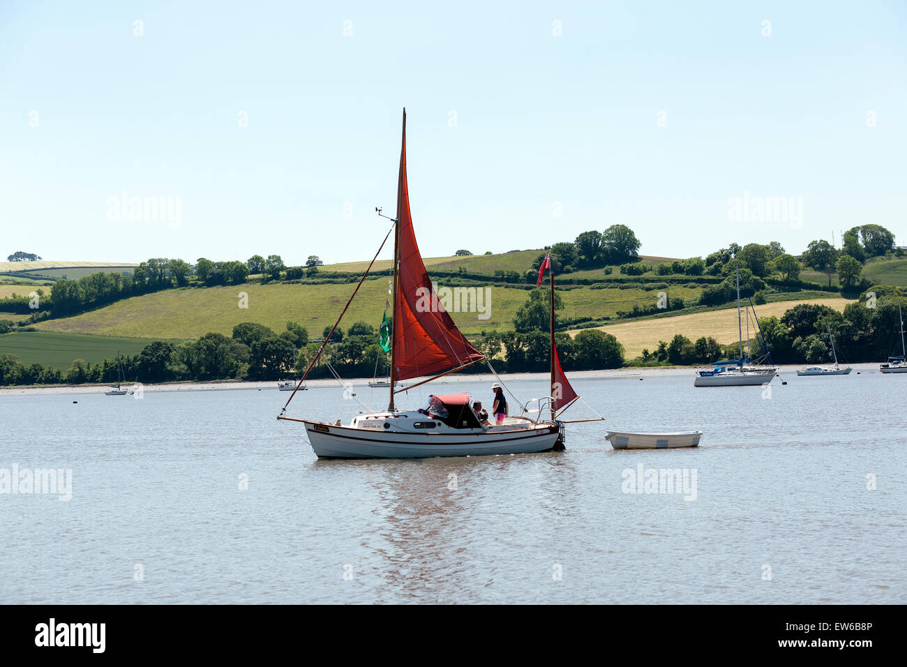 red sailed drifter boat on river dart,stoke gabriel,mill pond,moored, sea, ocean, coastal, coast, town, houses, - Stock Image