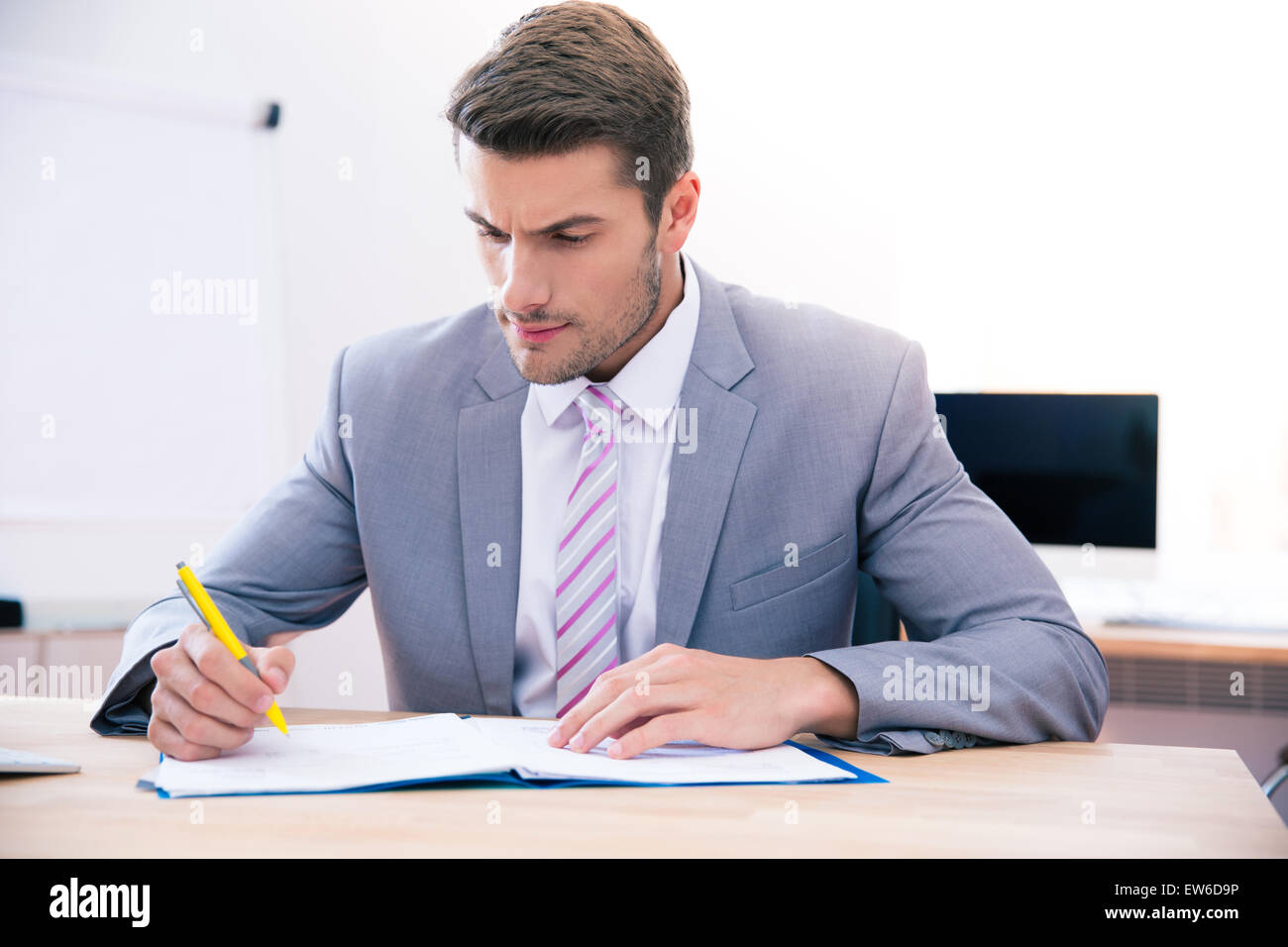 Confident businessman sitting at the table and signing document in office - Stock Image
