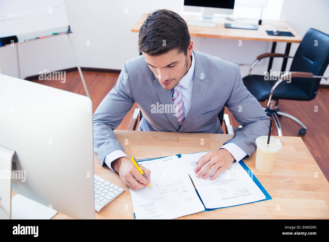 Businessman sitting at the table and signing document in office - Stock Image