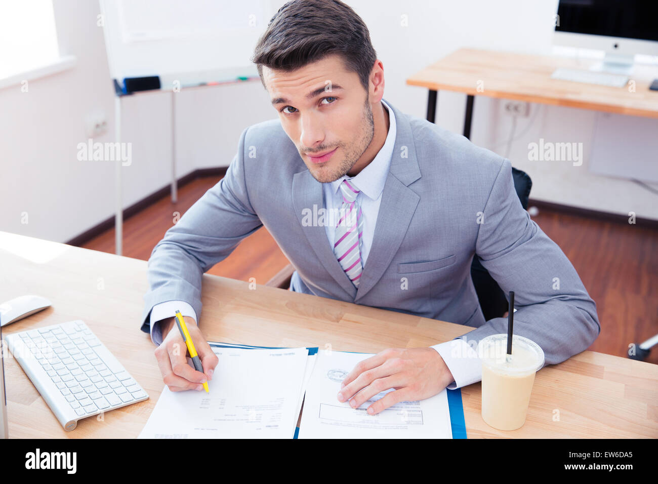 Handsome businessman signing document in office and looking at camera - Stock Image