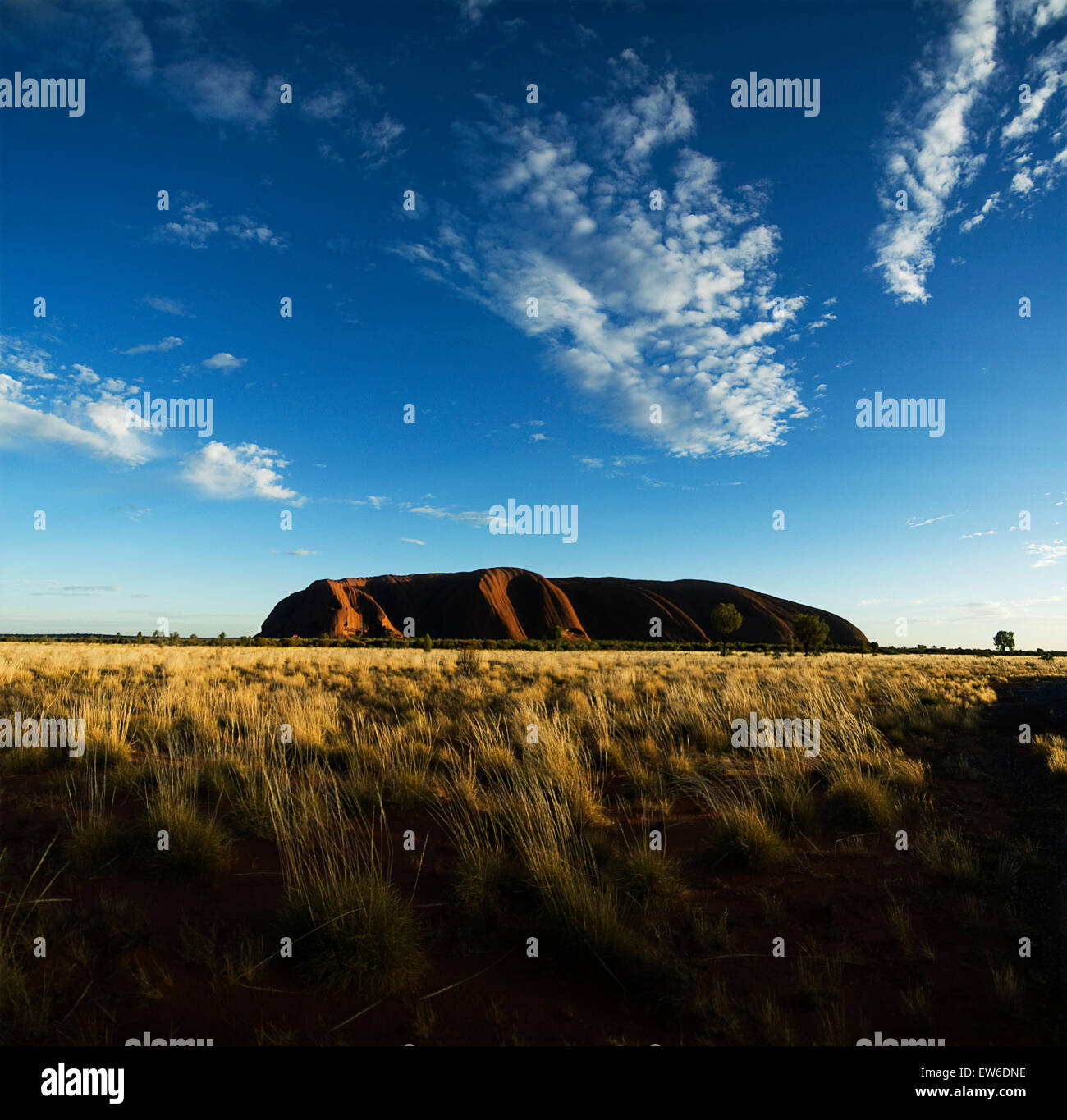 The sunrises over Uluru, Australia's sacred sandstone rock, more commonly known as Ayers Rock. - Stock Image