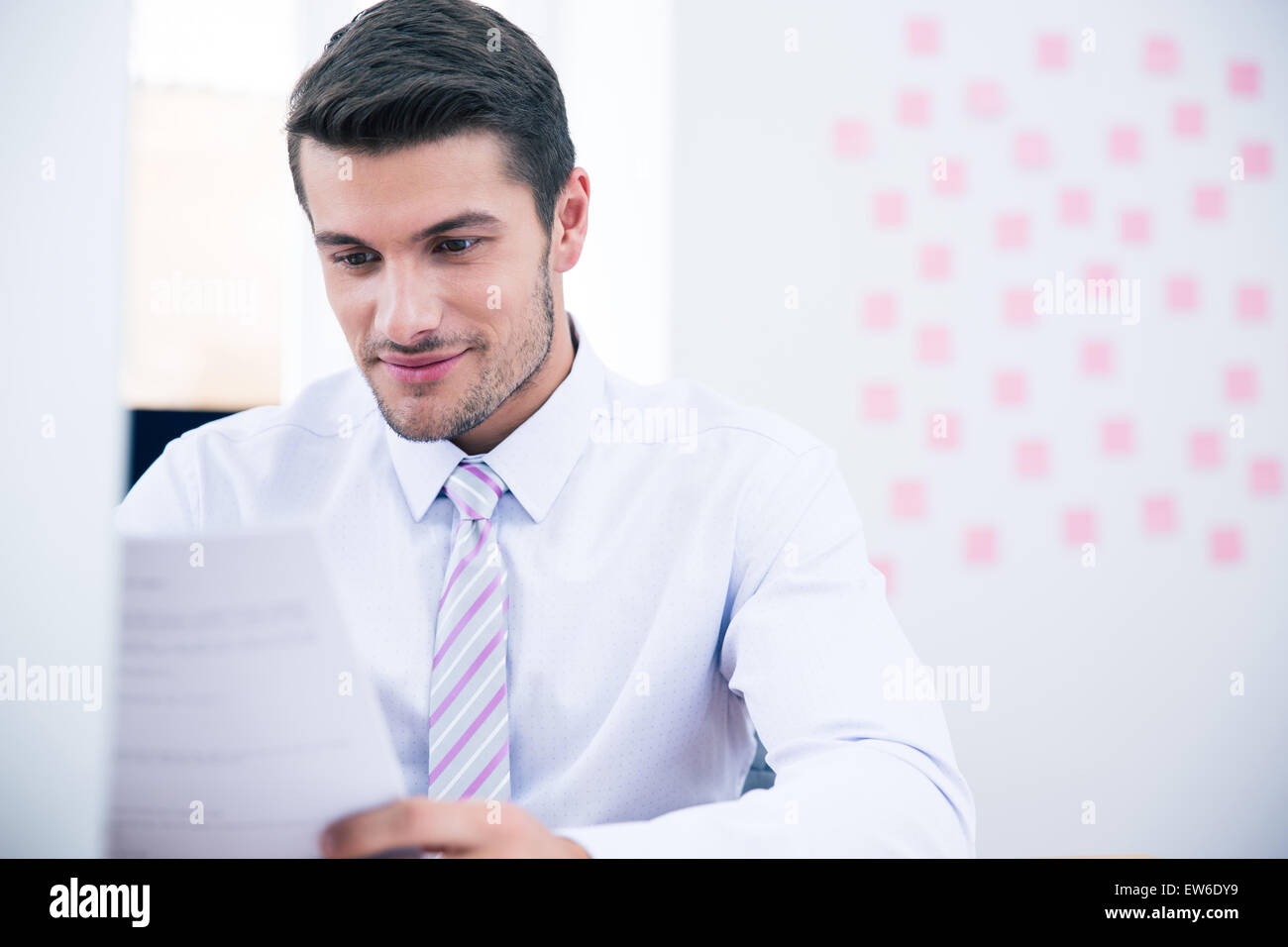 Handsome businessman reading document in office - Stock Image