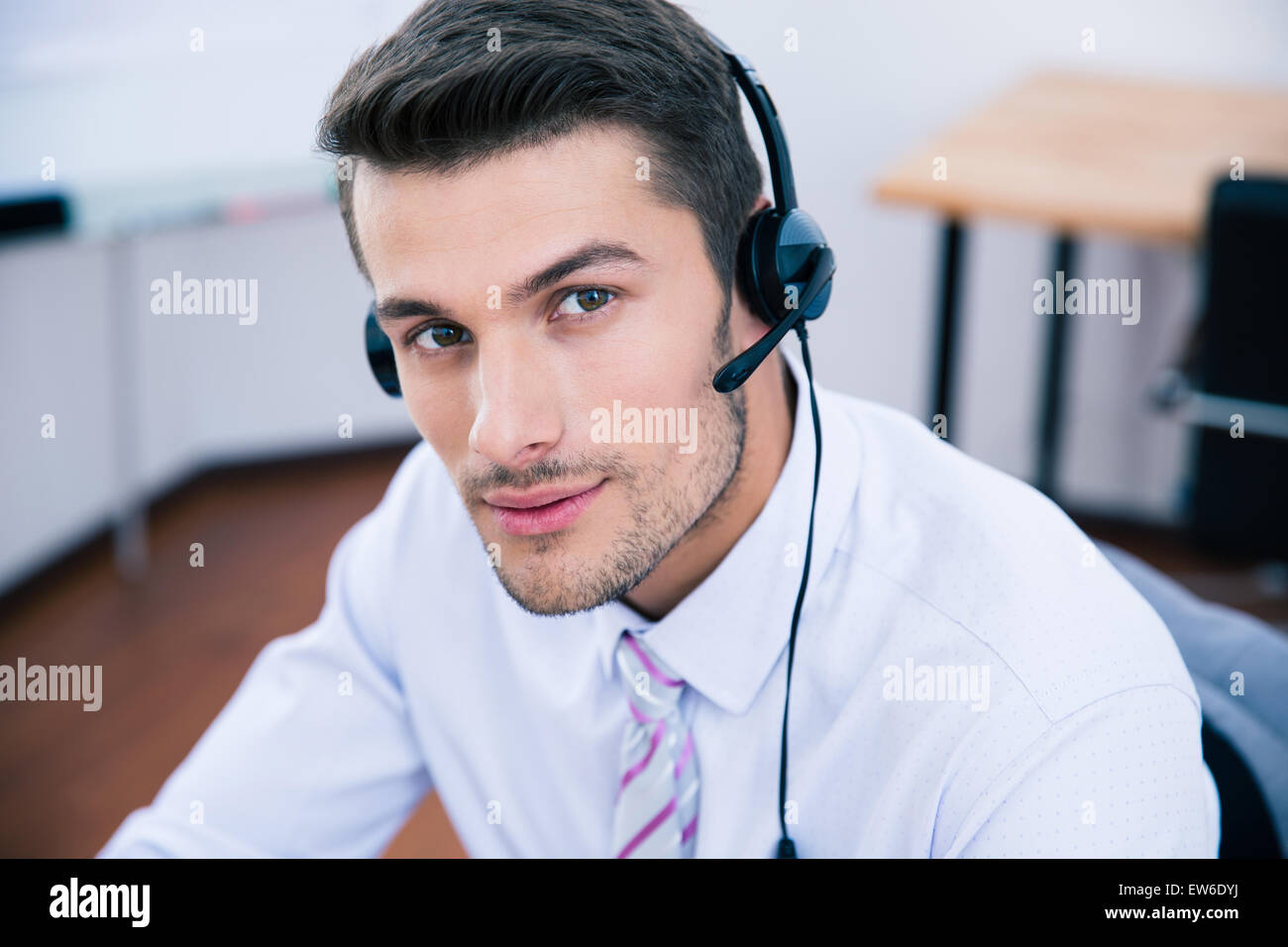 Portrait of a handsome male operator with headset looking at camera in office - Stock Image