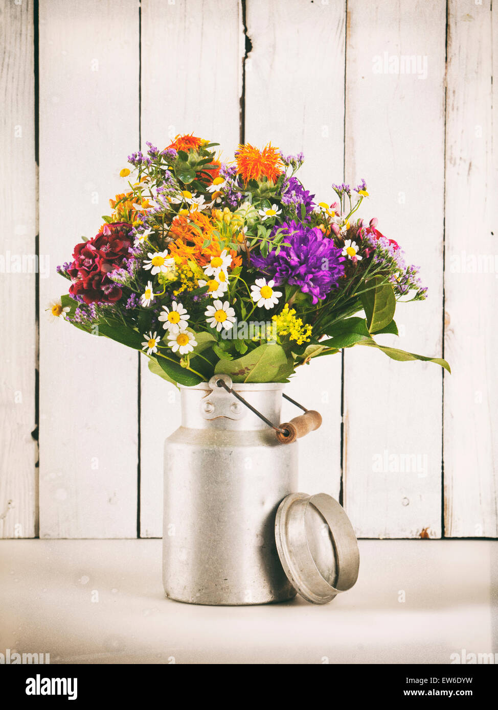 Summer flower bouquet in old milk canister in front of rustic wooden wall, vintage processing - Stock Image
