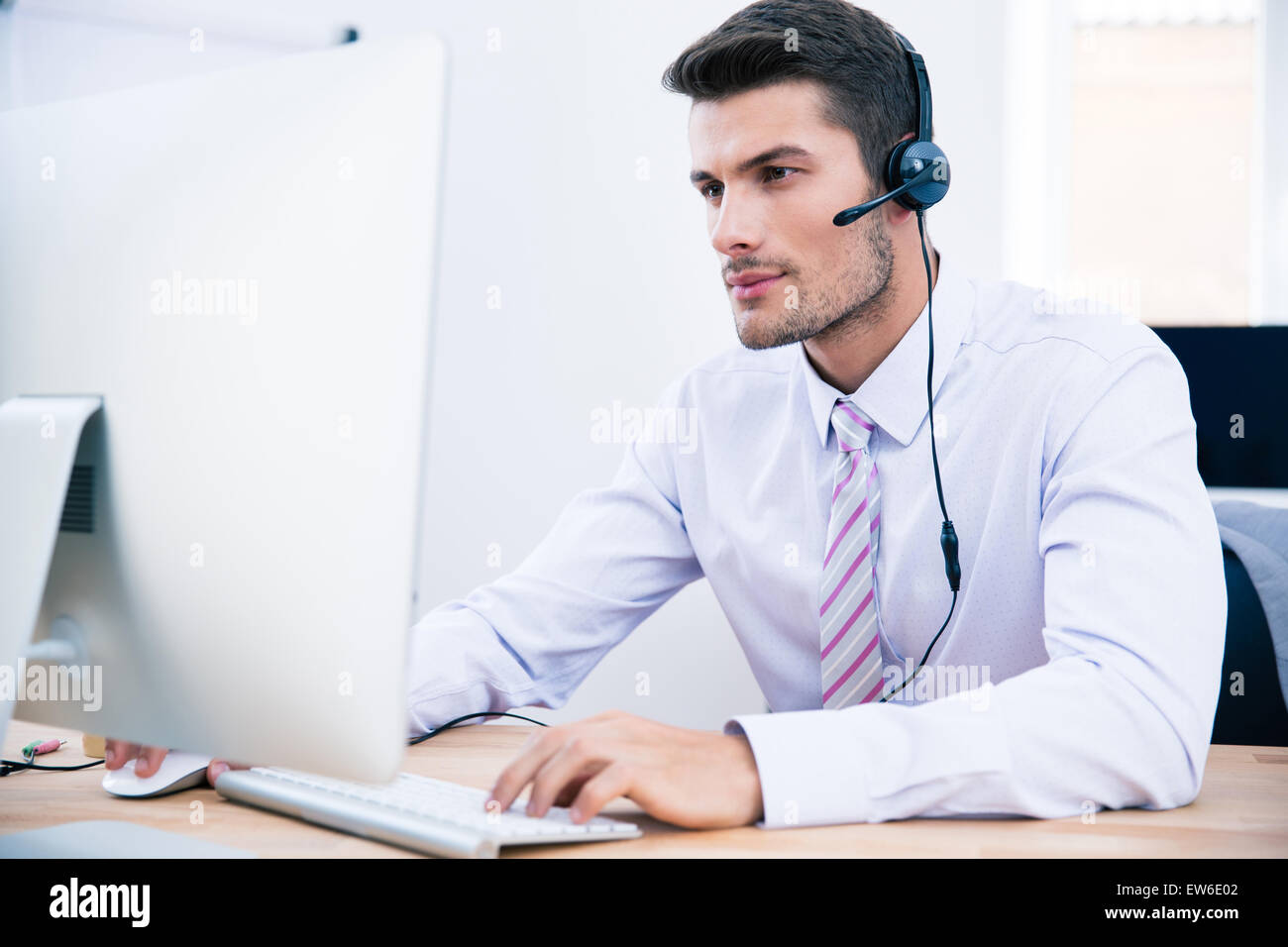Handsome male operator working on PC in office - Stock Image