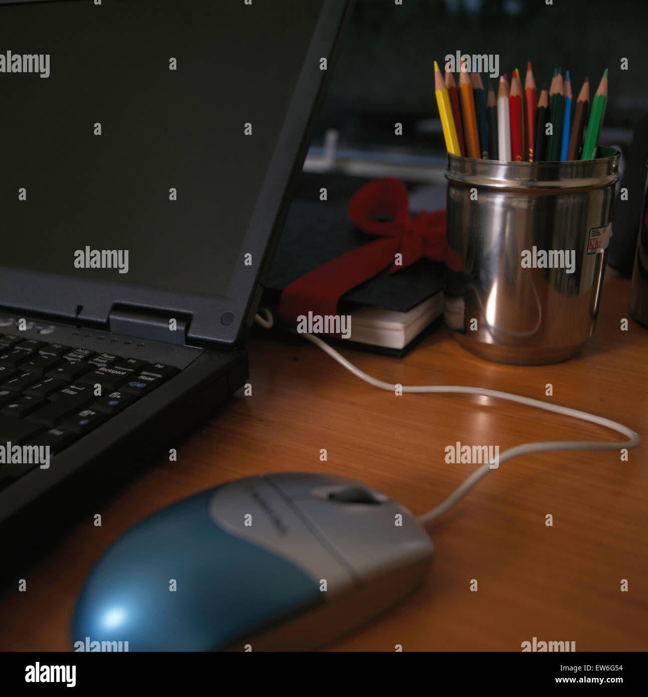 Close-up of laptop computer with mouse on desk with coloured pencils in silver pot - Stock Image