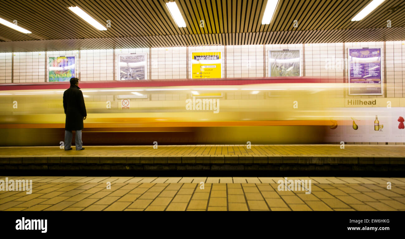 A man waits for the subway at the Hillhead stop in Glasgow, Scotland. - Stock Image