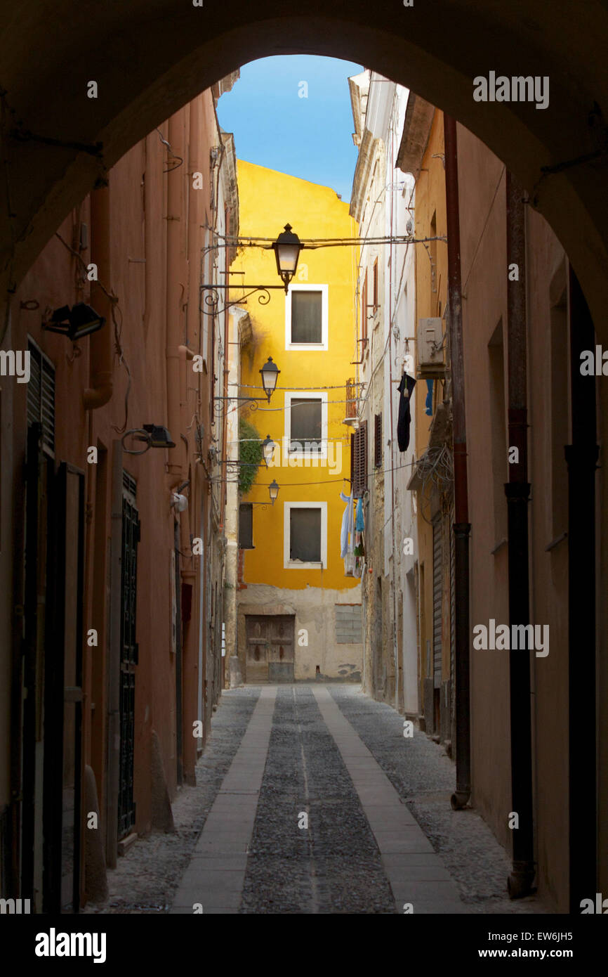Passageway leading to a bright yellow building in Sassari Old Town, Sardinia - Stock Image