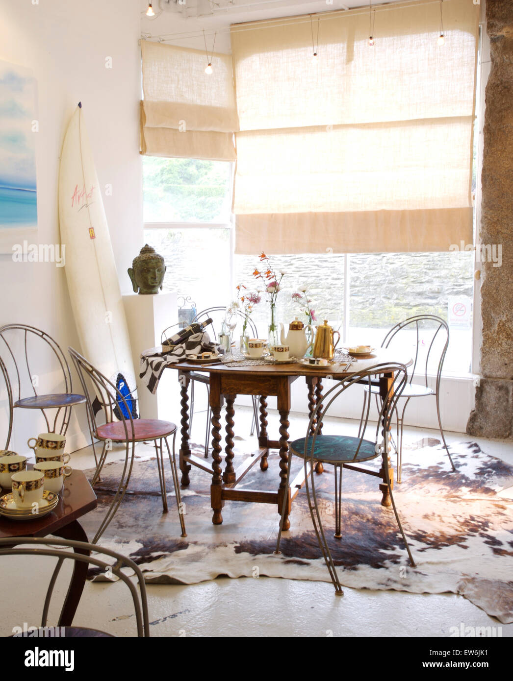 Metal chairs at Jacobean style table in coastal dining room with rough linen blinds on the windows Stock Photo