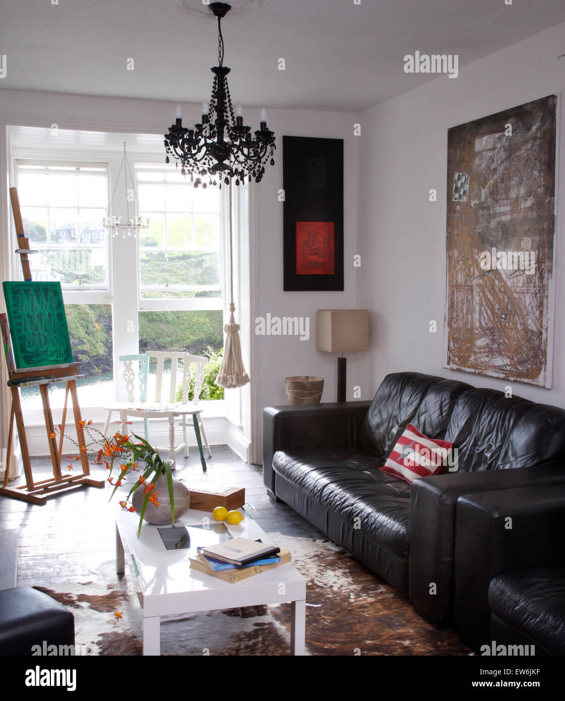 Black leather sofa in artists coastal living room with an easel beside open windows with a view of the sea