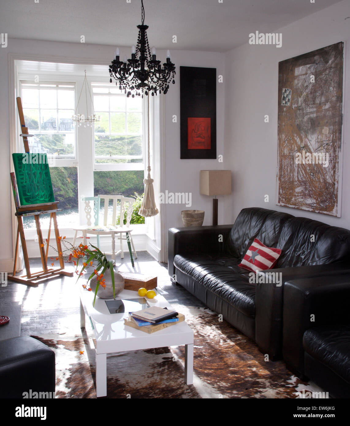 Black leather sofa and a white coffee table in artist\'s ...